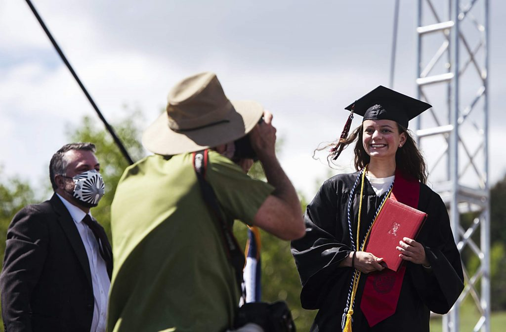 A graduate poses for the photographer on stage during Aspen High School's graduation at Buttermilk on Saturday, May 30, 2020. (Kelsey Brunner/The Aspen Times)
