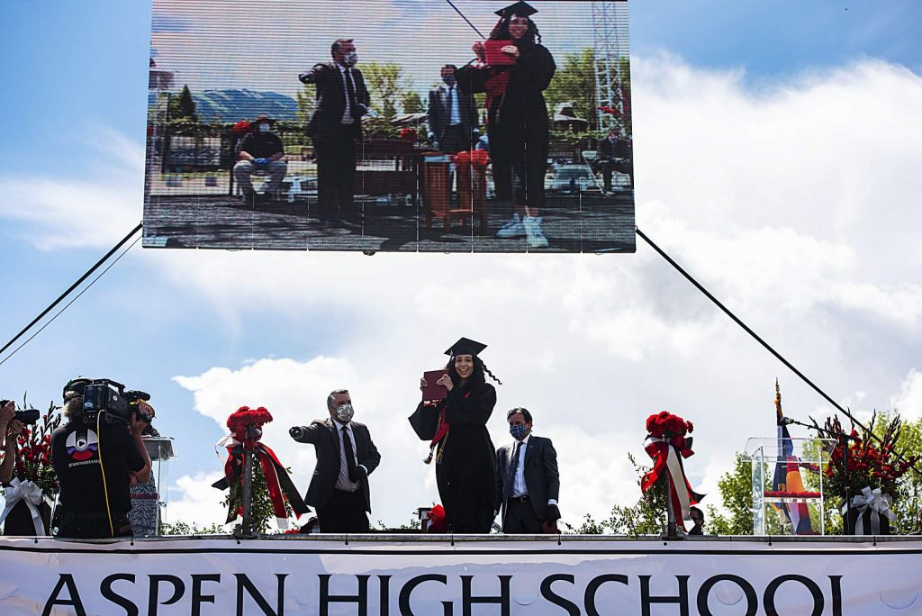 Janessa Diaz holds up her diploma holder as she crosses the stage during Aspen High School's graduation ceremony at Buttermilk on Saturday, May 30, 2020. (Kelsey Brunner/The Aspen Times)
