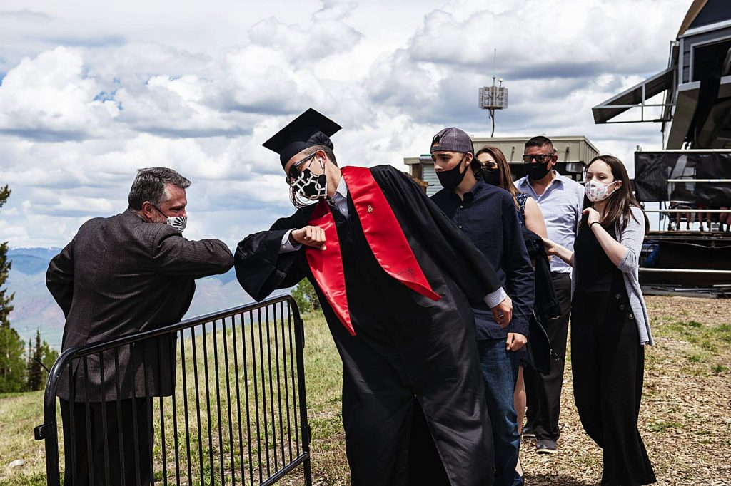 Principal Tharyn Mulberry bumps elbow with graduate Axel Quintanilla at the top of the mountain after Aspen High School's graduation at Buttermilk on Saturday, May 30, 2020. (Kelsey Brunner/The Aspen Times)