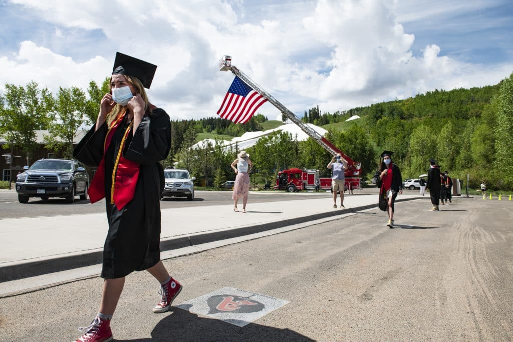A graduate prepares to take her mask off as she approaches the stage during Aspen High School's graduation ceremony at Buttermilk on Saturday, May 30, 2020.