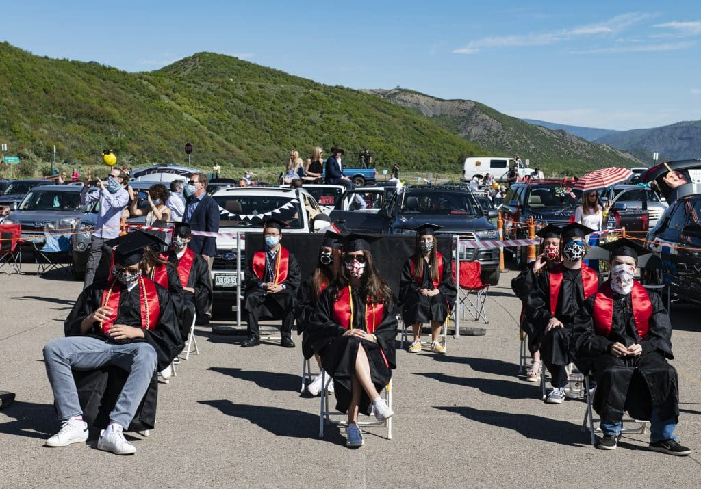 Graduates and parents watch the Aspen High School's graduation ceremony while social distancing at Buttermilk on Saturday, May 30, 2020.