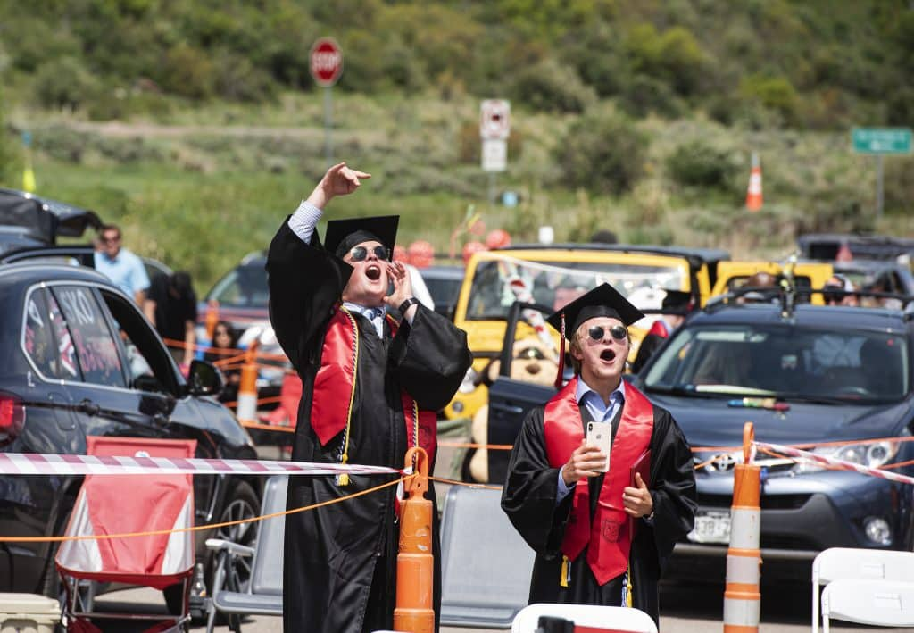 Graduates cheer on friends as they cross the stage during Aspen High School's graduation at Buttermilk on Saturday, May 30, 2020.