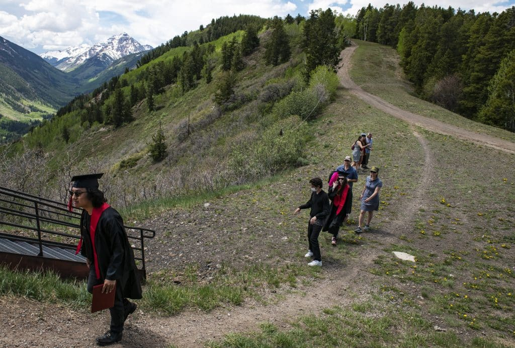 Graduates walk up the hill after taking photos in front of the Pyramid Peak view behind the Cliffhouse after Aspen High School's graduation ceremony at Buttermilk on Saturday, May 30, 2020.