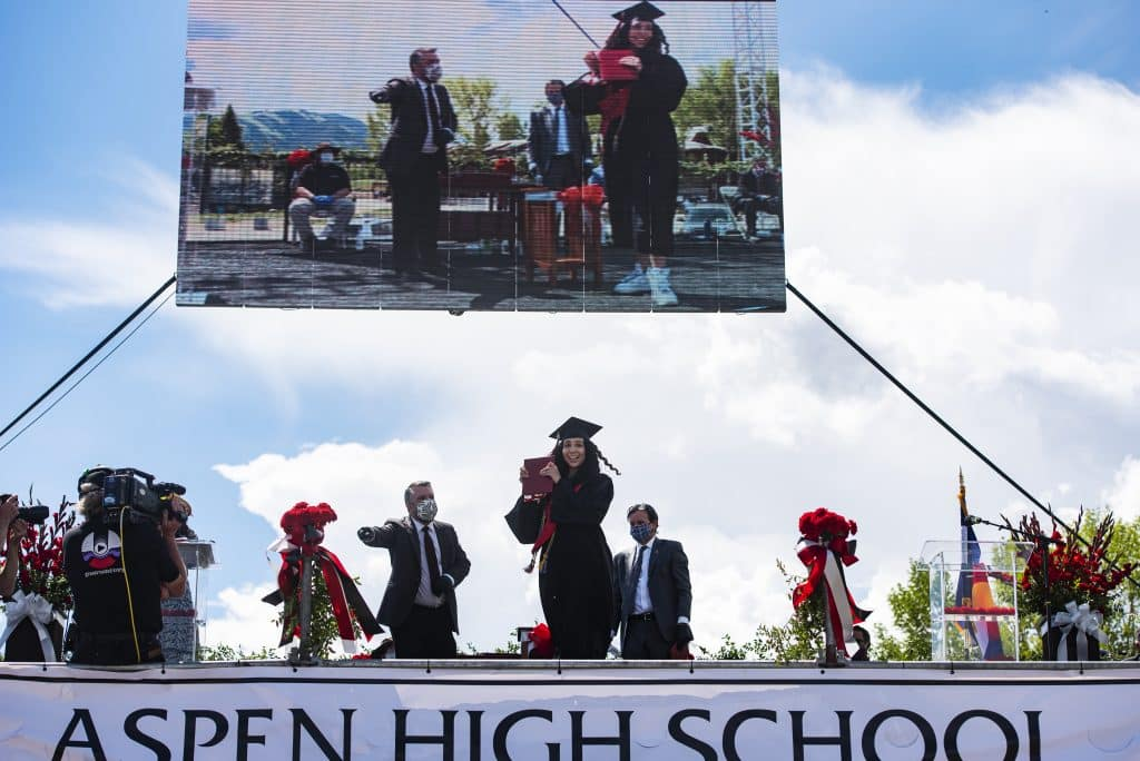 Janessa Diaz holds up her diploma holder as she crosses the stage during Aspen High School's graduation ceremony at Buttermilk on Saturday, May 30, 2020.