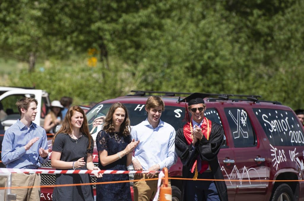 Connor Chesner, right, and family watch graduates cross the stage during Aspen High School's graduation at Buttermilk on Saturday, May 30, 2020.