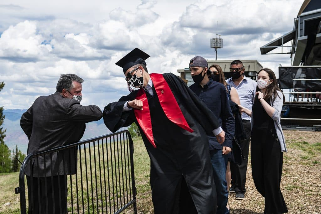 Principal Tharyn Mulberry bumps elbow with graduate Axel Quintanilla at the top of the mountain after Aspen High School's graduation at Buttermilk on Saturday, May 30, 2020.