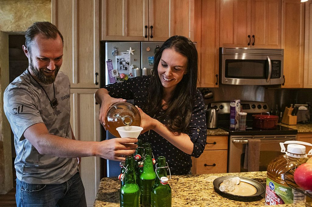 Derek Attema, left, holds the funnel as his wife Ryan Hile pours her home-brewed cider into bottles at their home in the Hunter Creek Apartments in Aspen on Tuesday, May 5, 2020. Both work in the restaurant industry in Aspen and have been out of work since the pandemic hit the town. Hile's mother taught her how to brew cider and the two have been trying to cut costs by making things at home. (Kelsey Brunner/The Aspen Times)