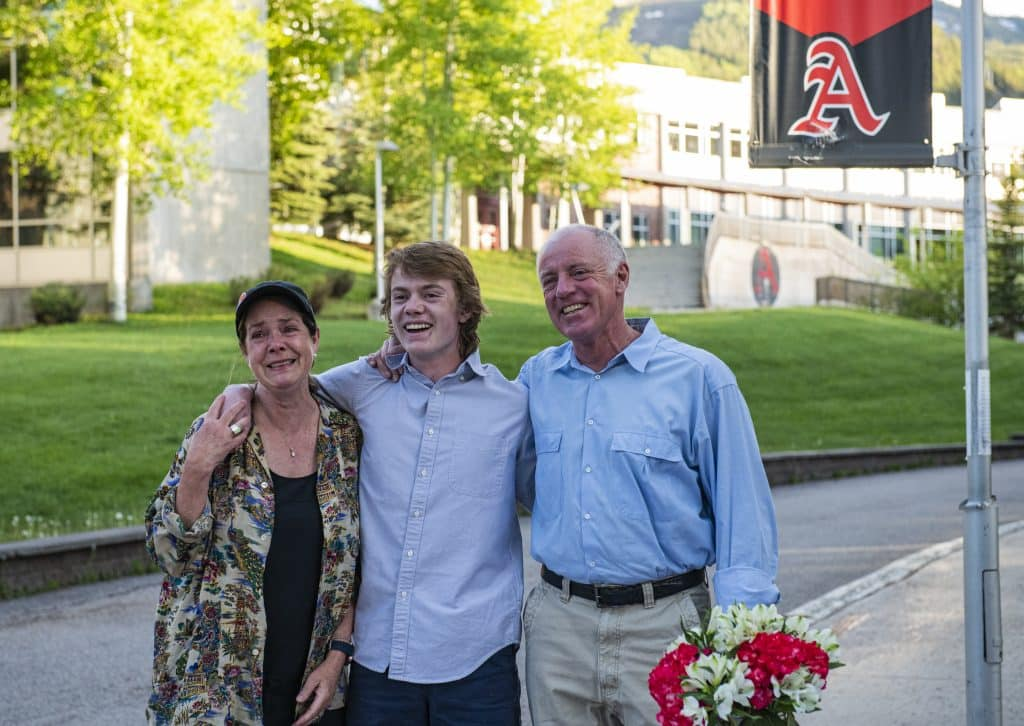 Eileen Seamans, left, Jack Seamans and Chip Seamans react as Jack's scholarships are announced by principal Tharyn Mulberry during the Aspen seniors drive-through scholarship event on Thursday, May 28, 2020. Eileen got emotional after Jack was awarded the Chapin Wright/Flatirons Scholarship.