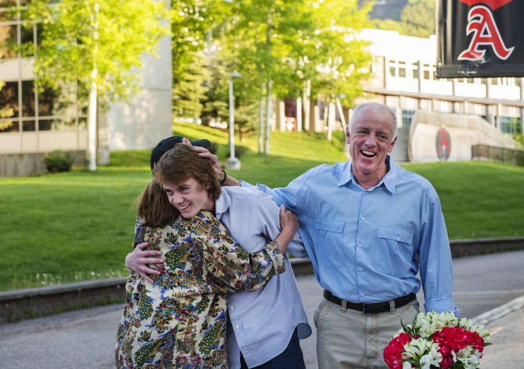 Eileen Seamans, left, Jack Seamans and Chip Seamans react as Jack's scholarships are announced by principal Tharyn Mulberry during the Aspen seniors drive-through scholarship event on Thursday, May 28, 2020. Eileen got emotional after Jack was awarded the Chapin Wright/Flatirons Scholarship. (Kelsey Brunner/The Aspen Times)