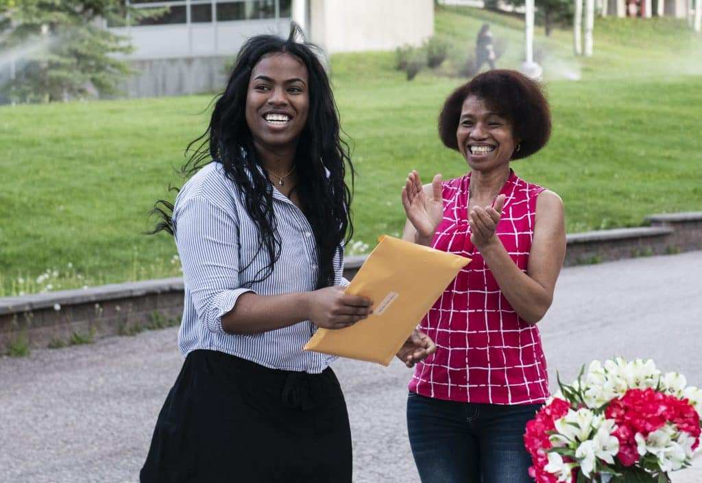 A student and her mother react after being awarded a scholarship during Aspen High School's drive-through event on Thursday, May 28, 2020.