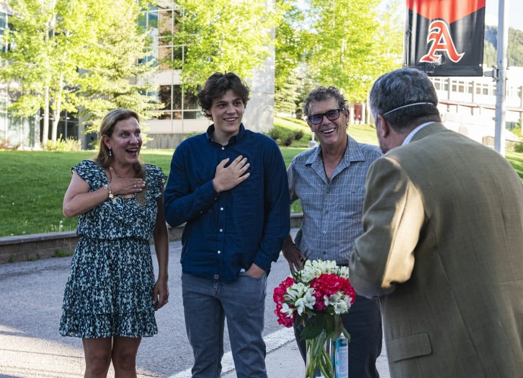 Aidan Ledingham, center, and his family react as he's announced as one of the two male athletes of the year at Aspen High School's drive-through scholarship event on Thursday, May 28, 2020.