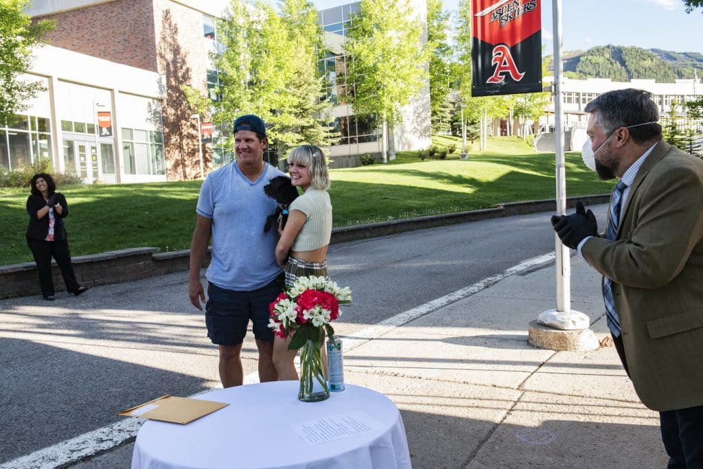 A student and her father pose for a photo after being awarded a scholarship during Aspen High School's drive-through event on Thursday, May 28, 2020.