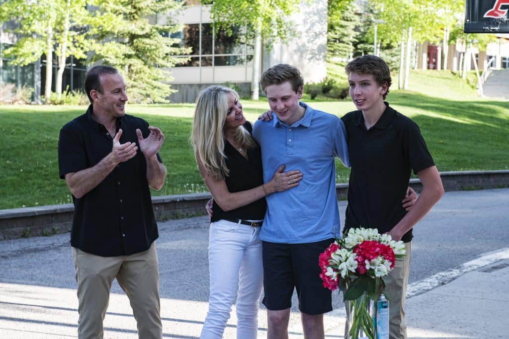 Jon Haisfield and his family react as his scholarships are announced during Aspen High School's drive-through event on Thursday, May 28, 2020.