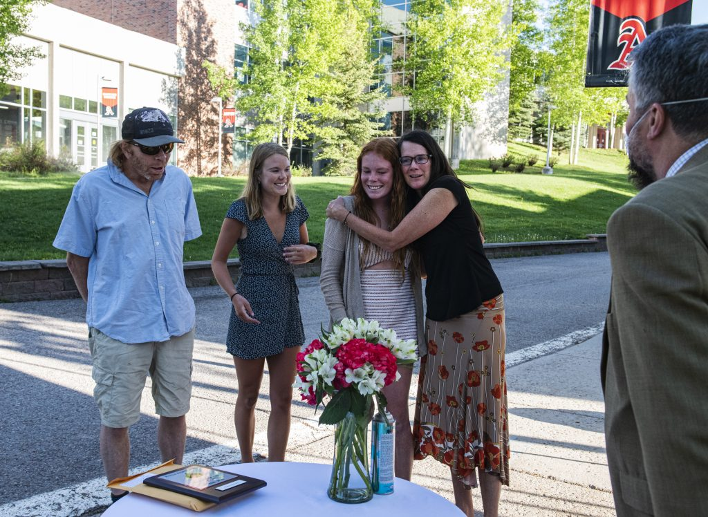 Maeve McGuire and her family react after she was announced as one of two female athletes of the year during Aspen High School's scholarship drive-though event on Thursday, May 28, 2020.