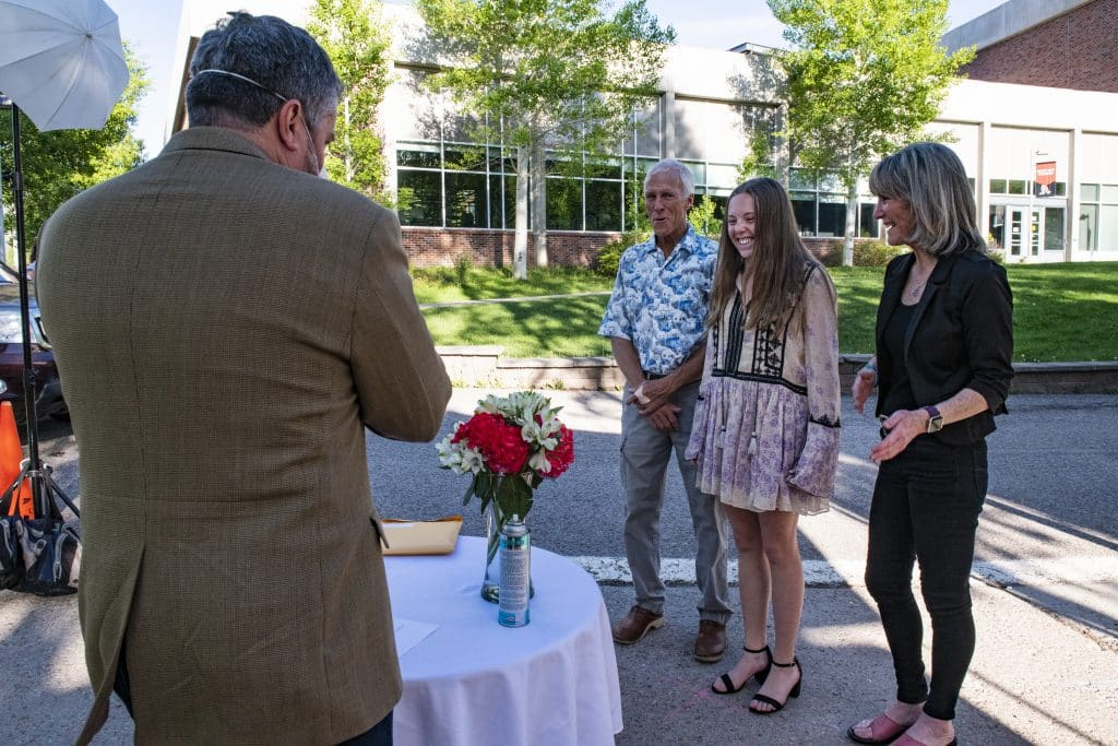 Greta Hansen, center, and her parents Eric and Kelly Hansen react as she's awarded scholarships during Aspen High School's drive-through event on Thursday, May 28, 2020.