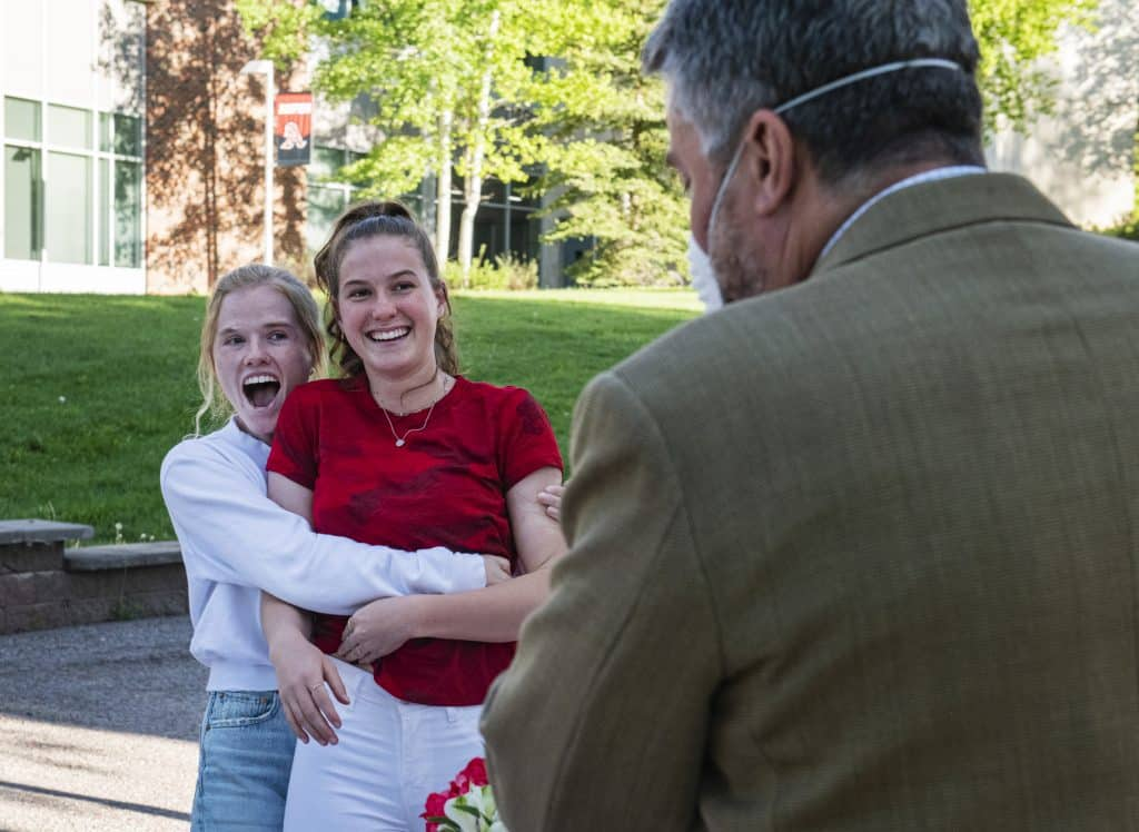 Jamie Howie, left, hugs her sister as she's announced as one of the two female athletes of the year during the Aspen High School scholarship drive-through event on Thursday, May 28, 2020.
