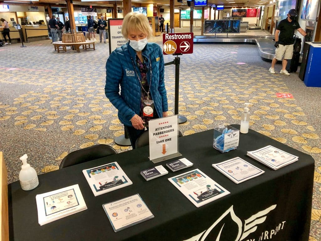A volunteer distributes masks and local health rule information at the Aspen airport on Memorial Day.