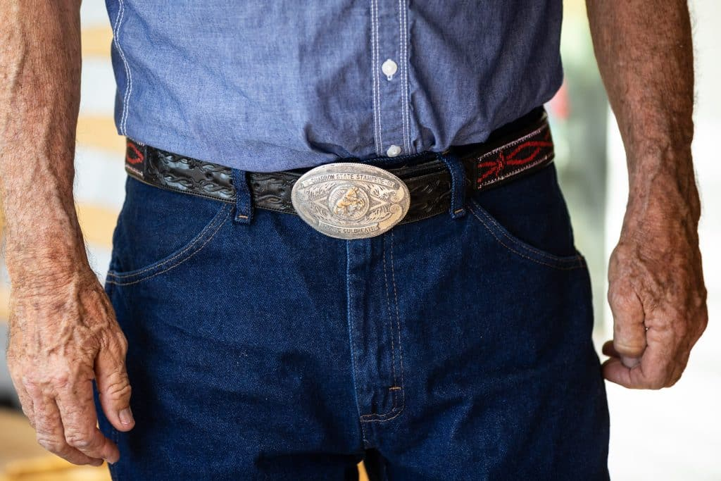 Photographed on his Heeney ranch on May 30, George Culbreath wears a trophy belt buckle for winning the 1961 Nebraska State Stampede State Stampede championship for saddle bronc.