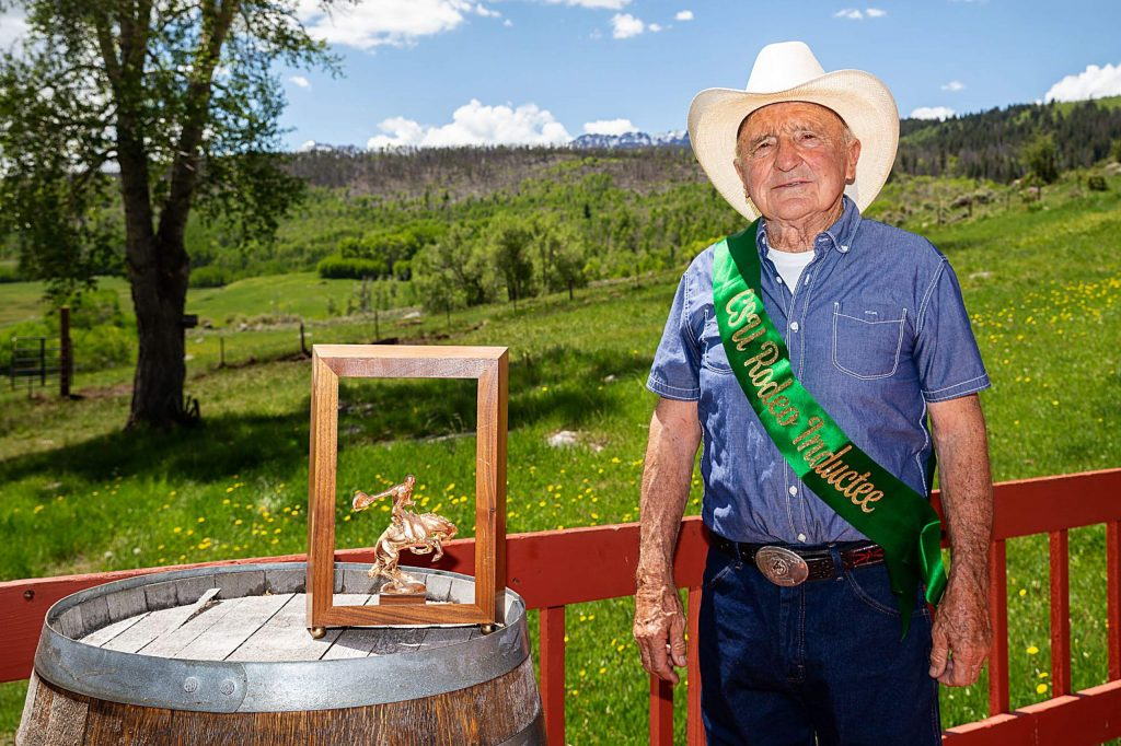 Standing with one of his trophies and championship belt buckle, Rodeo Hall of Fame inductee George Culbreath is photographed at his Heeney ranch on May 30.