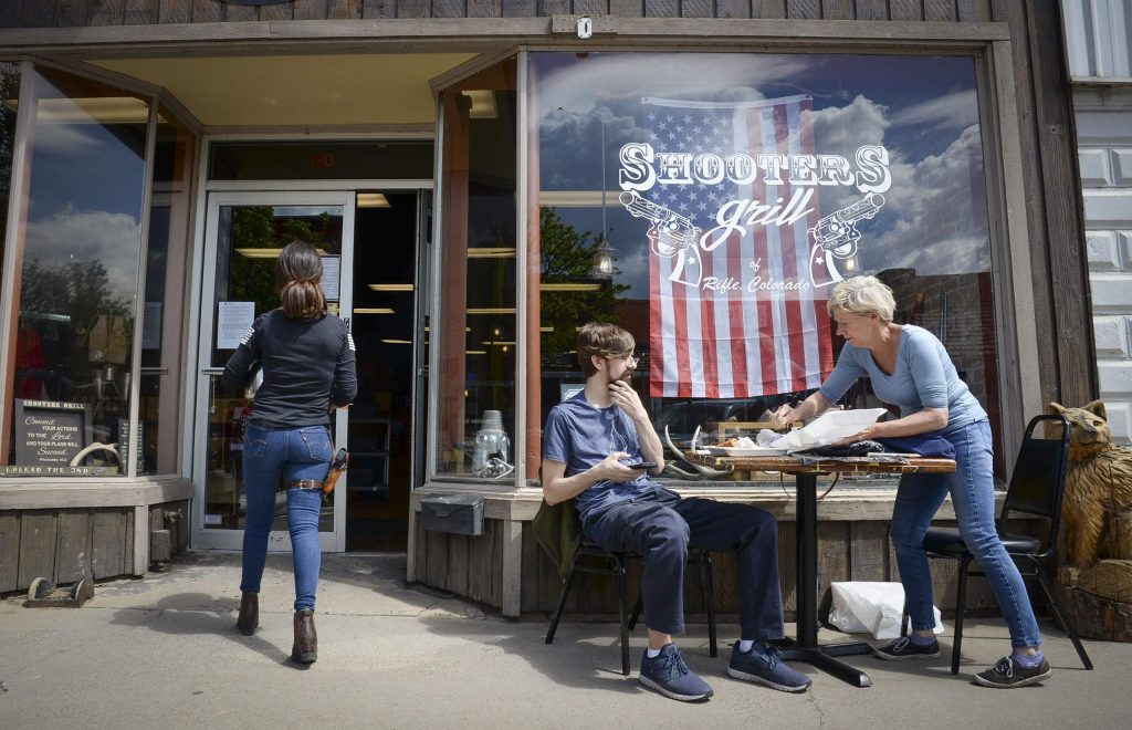Matthew Palomvi talks with his mother Sandra, who is visiting from Minnesota, after they had breakfast at Shooter Grill in Rifle on May 14. In defiance of a cease and desist order Shooter's owner Lauren Boebert opened her business to customers outside of her Third Street business on May 14.