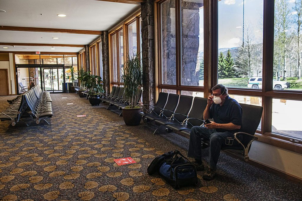 Mike Weddell secures his mask to go through TSA at the Aspen/Pitkin County Airport on Friday, May 1, 2020. Weddell is flying to Tallahassee, by way of Salt Lake City and Atlanta airports, to meet his wife and drive her back home. (Kelsey Brunner/The Aspen Times)