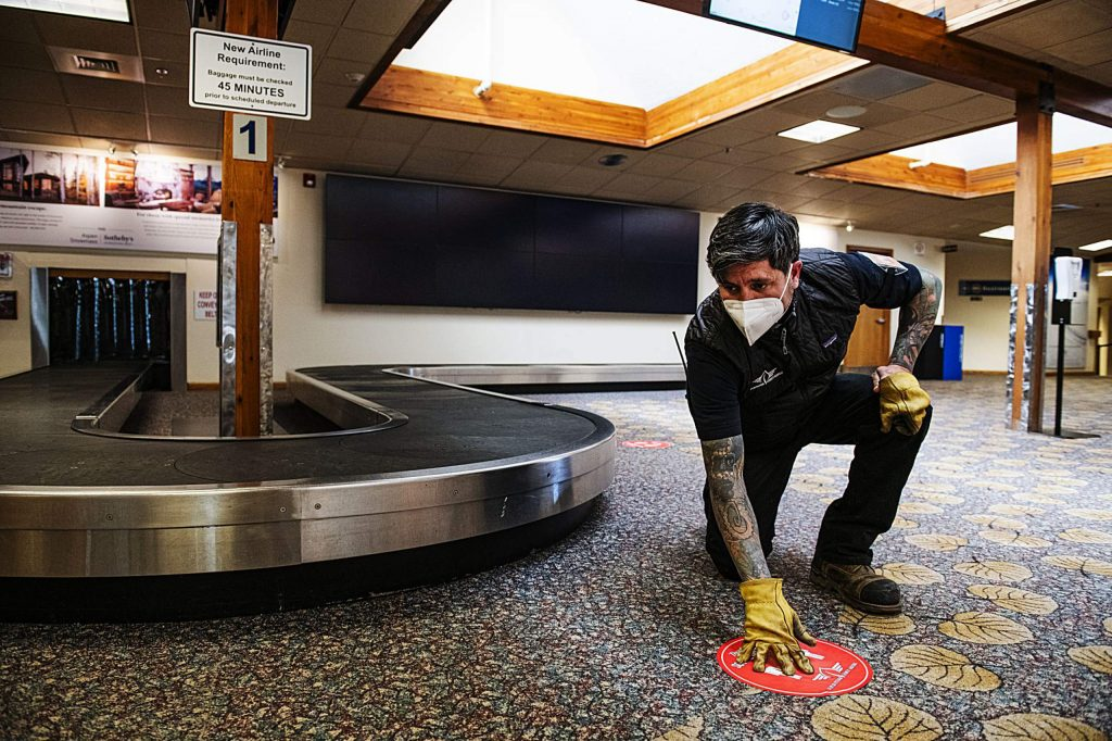 Aspen/Pitkin County Airport facilities manager Greg Boyd pushes the social distancing circles onto the floor around the baggage carousel on Friday, May 1, 2020. Boyd said there were 35 passengers expected to fly in and out of the airport that day. He explained that most days over the last couple of weeks had less than twenty, one day was down to five passengers, and that he hoped that people continued to social distance within the airport. (Kelsey Brunner/The Aspen Times)