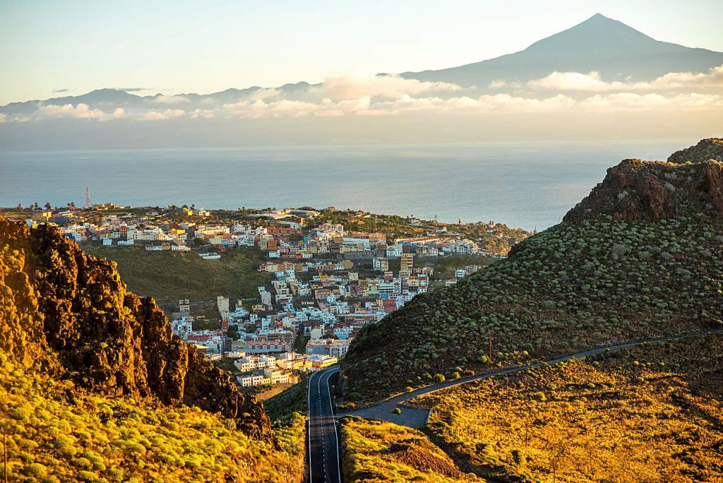 Landscape view on mountain road and San Sebastian city with Tenerife island on the background in the morning