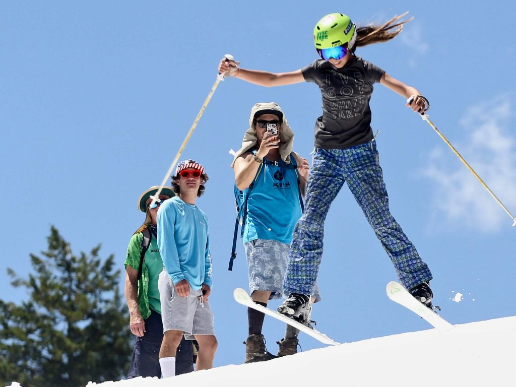 Aspen Valley Ski and Snowboard Club coaches, including Olympic silver medalist Alex Ferreira, middle left, watch as Kaiya Torres goes off a jump on Thursday, June 27, 2019, during the AVSC Glacier Camp at Buttermilk Ski Area. (Photo by Austin Colbert/The Aspen Times)