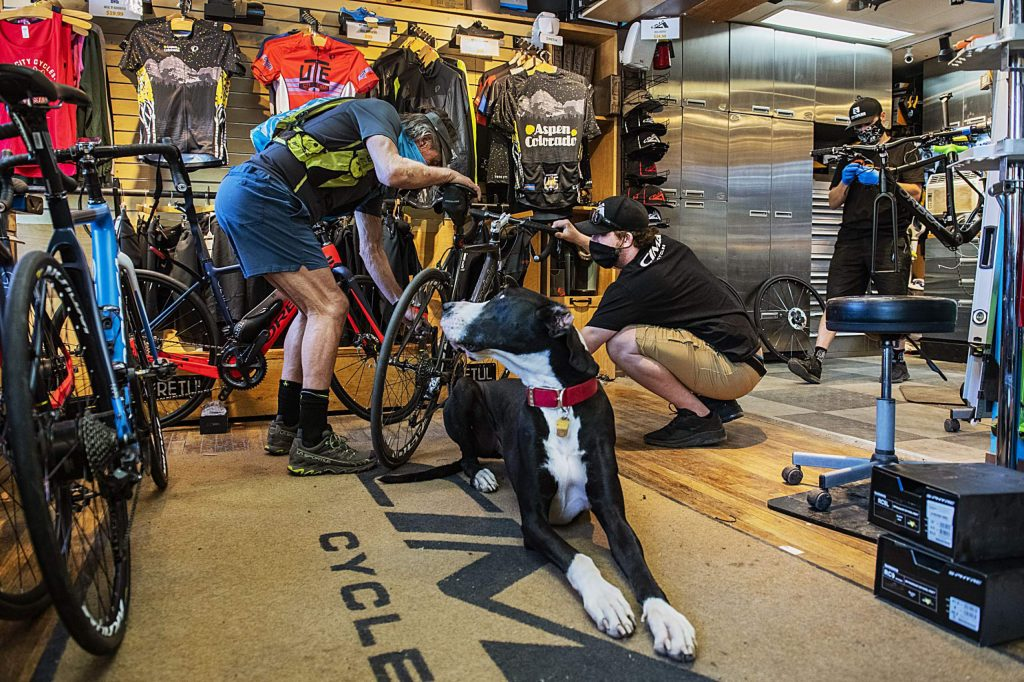 Ute City Cycles shop dog Cooper looks back as owner PJ Clotfelter, center right, helps customer Danny Patterson with his bike and Greg Saxton, right, works on another bike on Friday, May 22, 2020. (Kelsey Brunner/The Aspen Times)