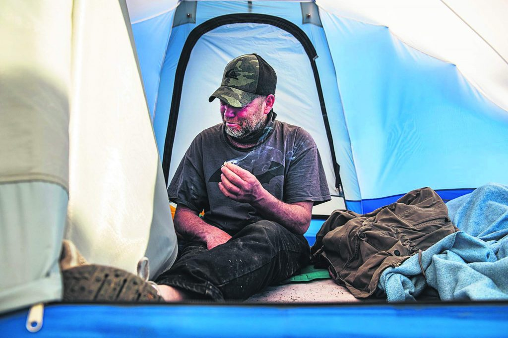 Vince Thomas gets emotional in his tent while smoking a cigarette in the homeless camp on Wednesday, May 13, 2020. Thomas explained that he has been homeless since he and his wife divorced years before. He has been in Aspen for about five years. Thomas felt passionately that affordable housing should be available for people in need in the valley.