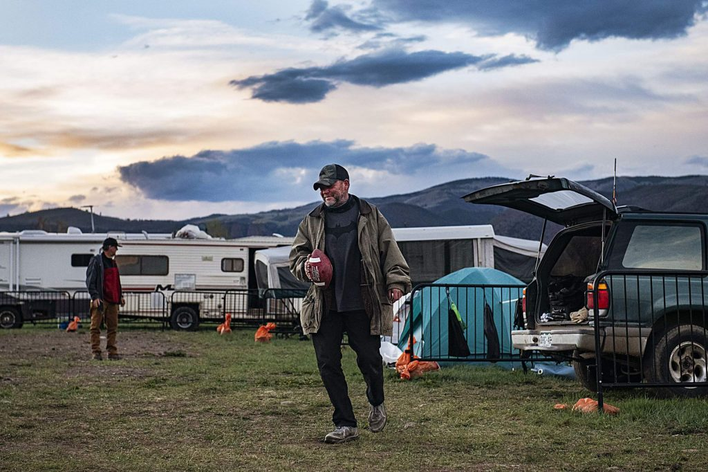Charlie, left, and Vince Thomas pass the football in the Aspen homeless camp after dinner on Tuesday, May 12, 2020. The two shared laughs as Vince pretended to throw the ball to Charlie and fake him out.
