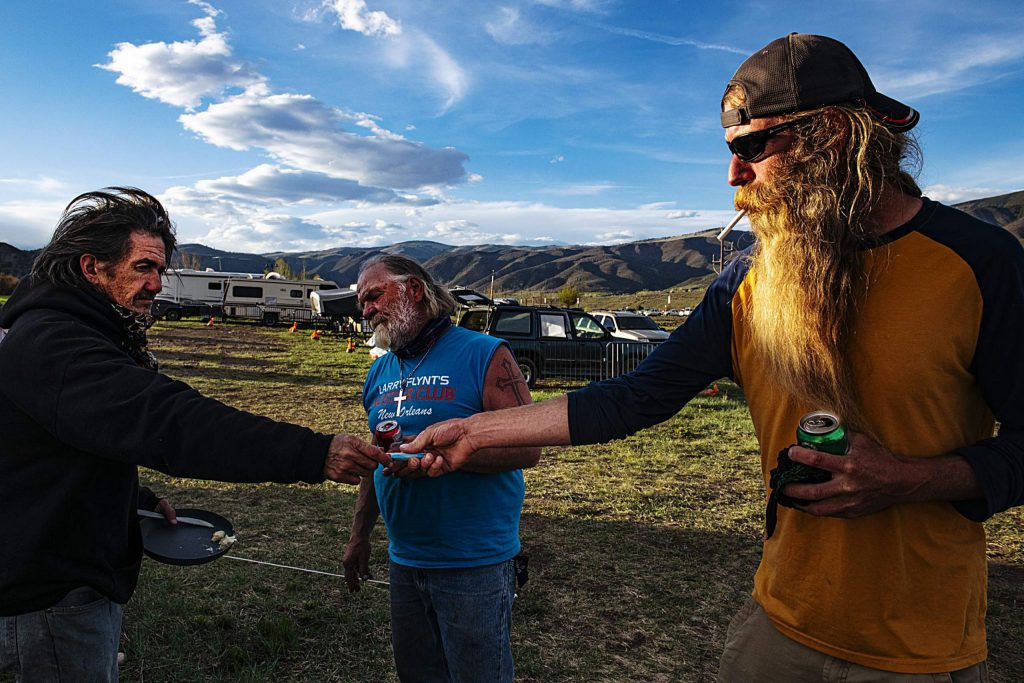 Dale Hughes, left, hands Jeremy Brockway a lighter as they talk to James Hoge, center, at the homeless camp in Aspen on Tuesday, May 12, 2020.