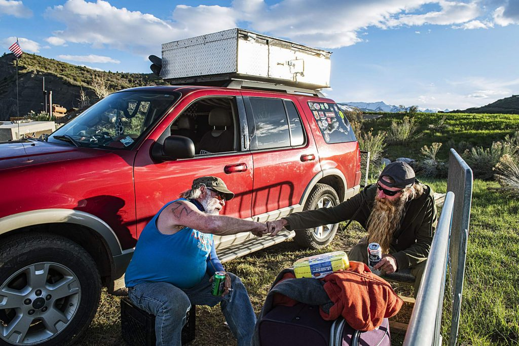 James Hoge and Jeremy Brockway fist bump while drinking a beer and talking outside of Hoge's car at the homeless camp in Aspen on Wednesday, May 13, 2020.