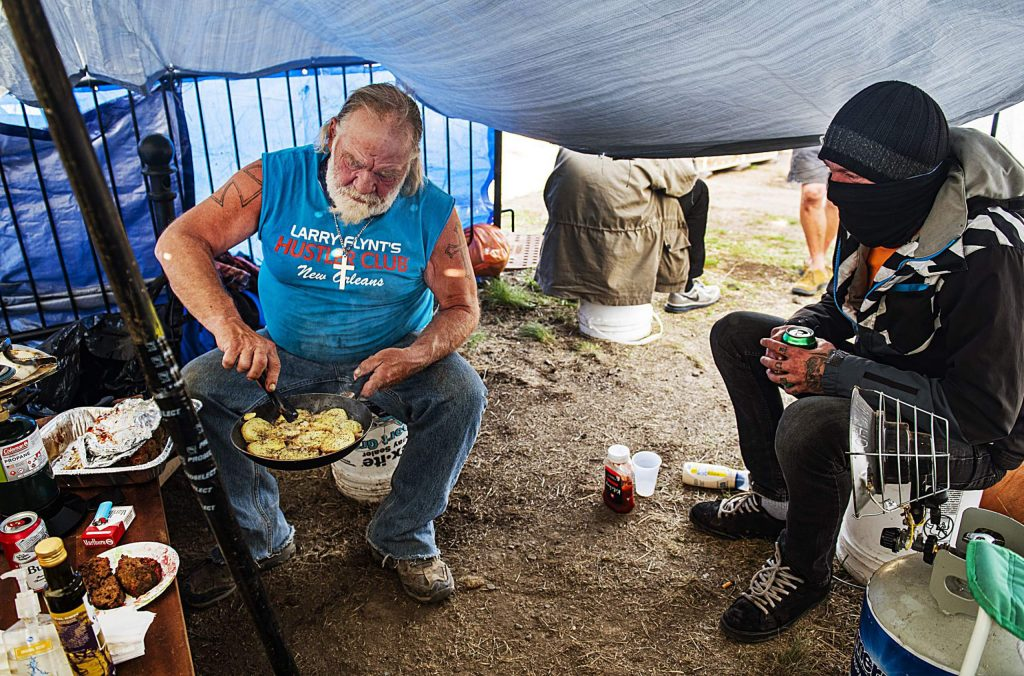 James Hoge prepares potatoes and meatloaf for dinner at the camp as Derich Hantel keeps him company in the communal tent at the homeless camp on Tuesday, May 12, 2020. The Aspen Homeless Shelter brings food to the camp for the evening meal and the clients communally prepare the meals.