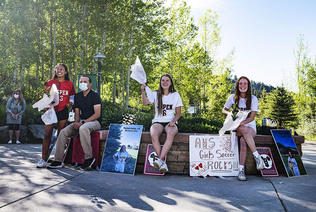 Aspen's girls soccer seniors Karen Galvan, left, Payton Curly and Maeve McGuire watch with their families as their team has a mini drive-by parade with signs and honking to honor them during a rose ceremony in the Aspen Recreation Center parking lot on Monday, May 18, 2020. (Kelsey Brunner/The Aspen Times)