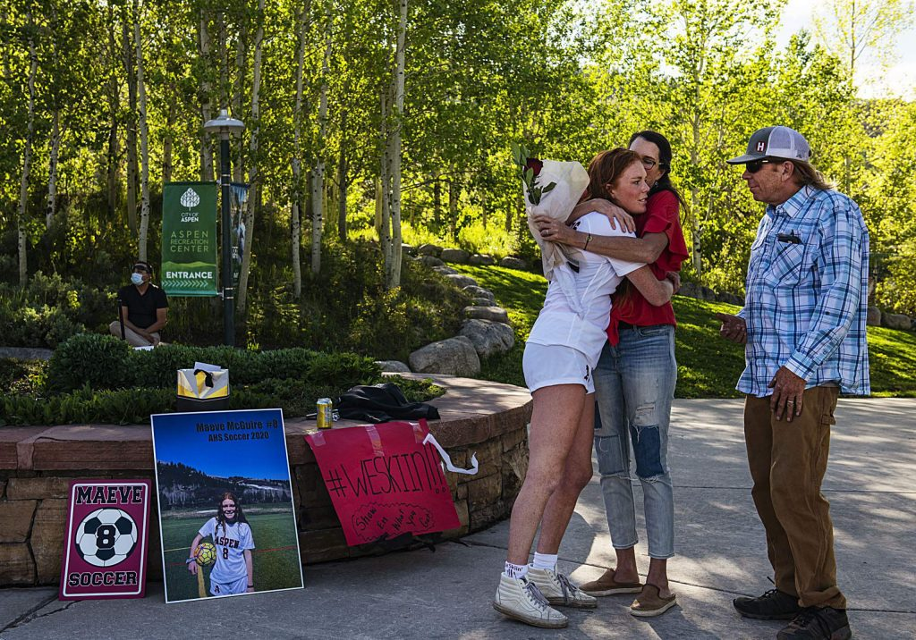 Aspen Senior Maeve McGuire hugs her mom and dad after the rose ceremony for the senior girl's soccer players on Monday, May 18, 2020. (Kelsey Brunner/The Aspen Times)