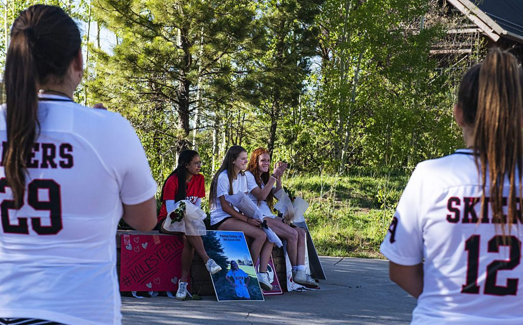 Teammates of the Aspen's girls soccer seniors Karen Galvan, left, Payton Curly and Maeve McGuire cheer for them during a drive-by parade with signs and honking to honor them during a rose ceremony in the Aspen Recreation Center parking lot on Monday, May 18, 2020. (Kelsey Brunner/The Aspen Times)