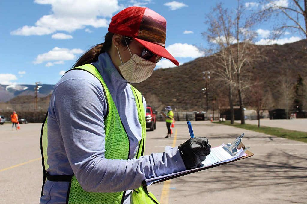 Erin Kinney, case manager with Aspen Family Connections, registers locals before they collect their free food at the family resource center's first distribution day in Snowmass Village on May 1, 2020.