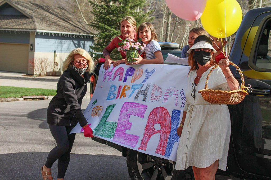 Leah Moriarty stands with neighbors who drove by with a homemade happy birthday sign on May 3, 2020.