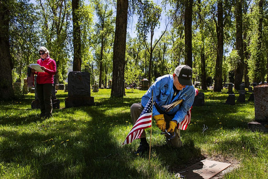 """Jane Stemsrud, left, checks the Red Butte Cemetery registry as Dan Glidden places a flag on a veteran's grave on Friday, May 22, 2020. Stemsrud has been helping Glidden place flags for years, she explained, and her father and brother were both veterans. """"This is my way of paying respect and memorializing,"""" said Stemsrud. (Kelsey Brunner/The Aspen Times)"""