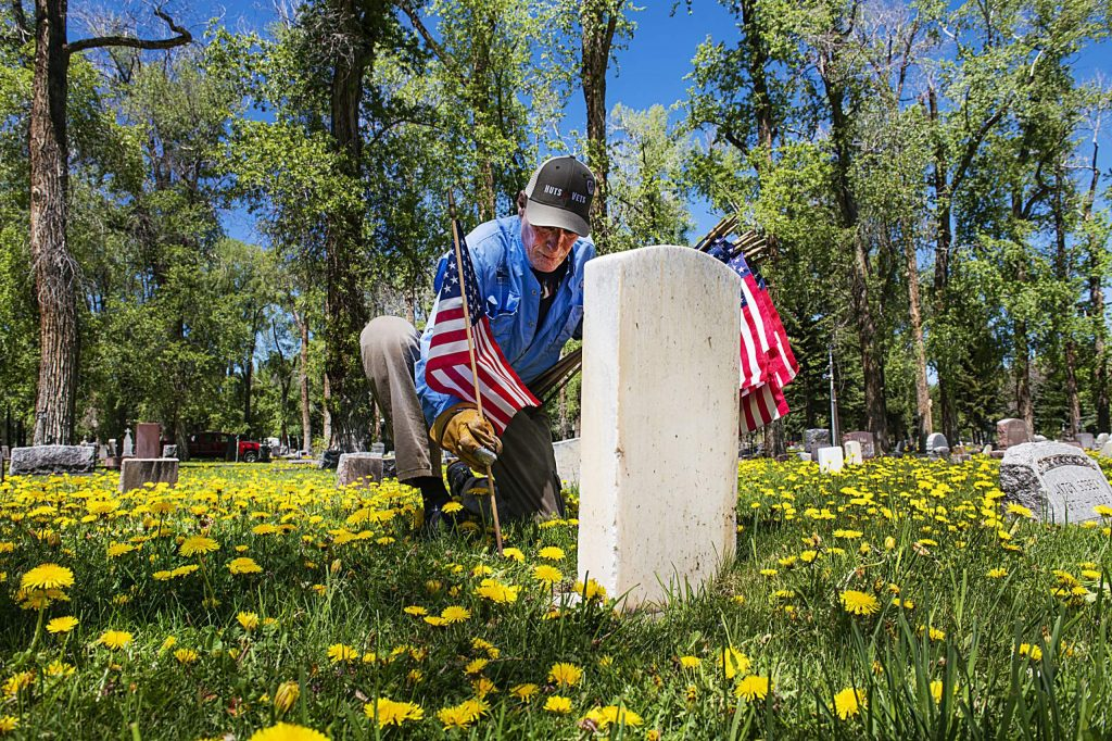 Veteran Dan Glidden places flags next to known veterans graves in the Red Butte Cemetery in Aspen on Friday, May 22, 2020. Glidden has been putting flags on graves in the city of Aspen for over fifteen years. (Kelsey Brunner/The Aspen Times)