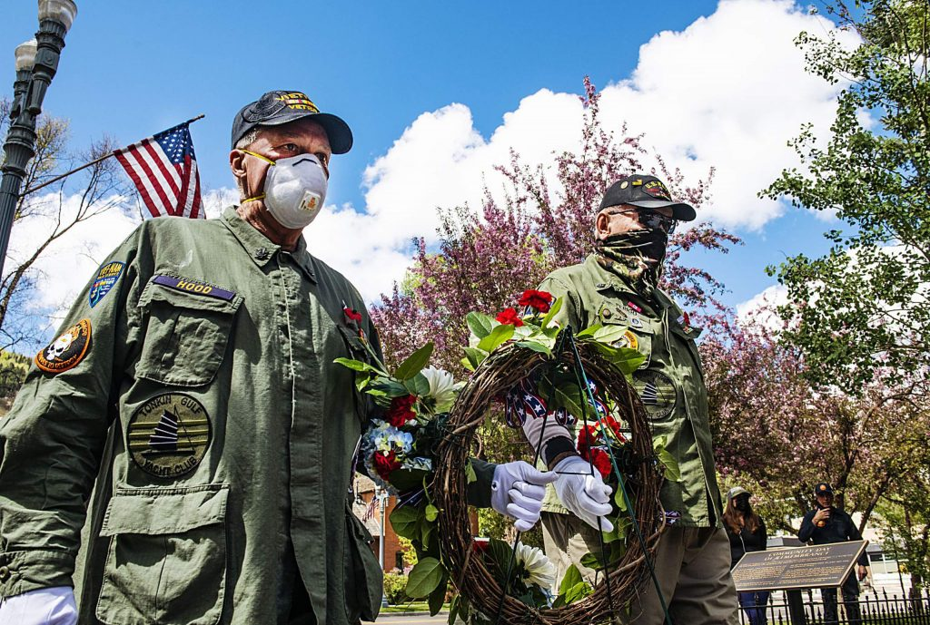 """Honor Guard and Vietnam veterans Palmer Hood, left, and Bob """"Gunny"""" Perigo carry the Memorial Day wreath at the Veterans Memorial in Aspen on Monday, May 25, 2020. (Kelsey Brunner/The Aspen Times)"""