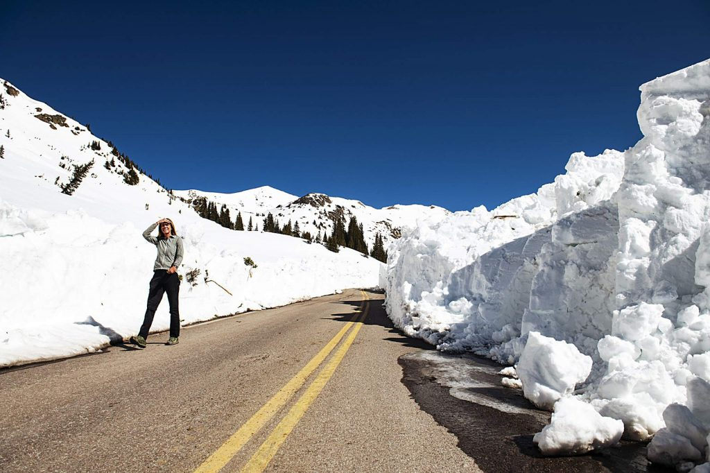 Independence Pass Foundation executive director Karin Teague walks down the road in between towering snow walls after CDOT cleared that section of road on Tuesday, May 5, 2020.