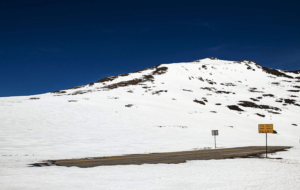 A melted part of the road at the Independence Pass summit peeks out from the snow on Tuesday, May 5, 2020.
