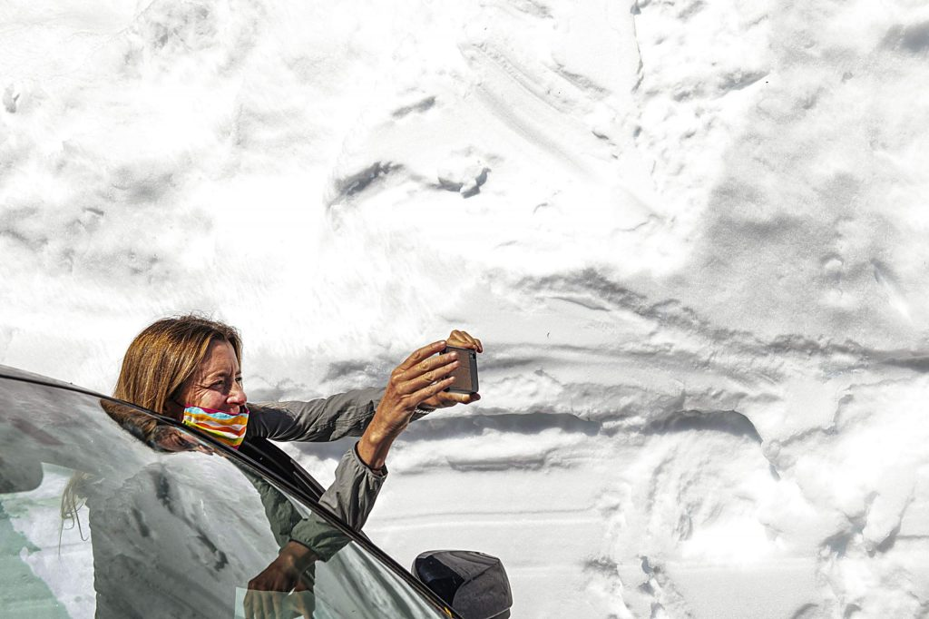 Independence Pass Foundation executive director Karin Teague takes a photograph of the high snow walls surrounding the road on Tuesday, May 5, 2020.
