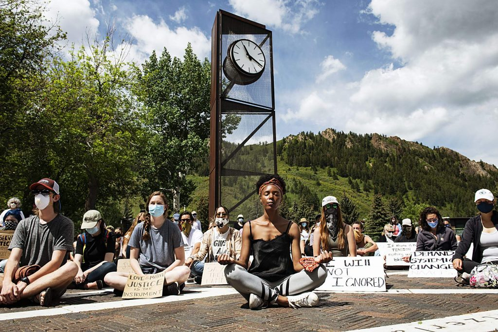 Jenelle Figgins, center, leads a moment of silent meditation before the protesters marched through Aspen's streets on Sunday, May 31, 2020. (Kelsey Brunner/The Aspen Times)