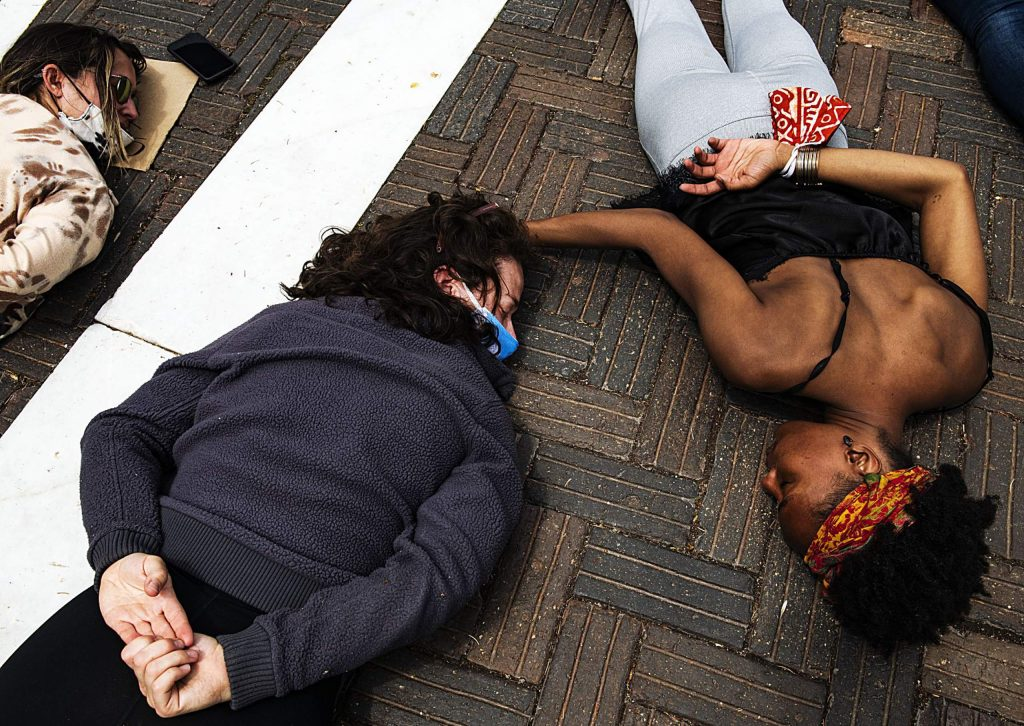 """Erica Joos, left, and Jenelle Figgins comfort each other as they lay on the ground for nine minutes to honor George Floyd during a peaceful protest in Aspen on Sunday, May 31, 2020. """"Nine minutes is a long time,"""" whispered Figgins. """"I can't breathe,"""" the protesters continued to chant. (Kelsey Brunner/The Aspen Times)"""