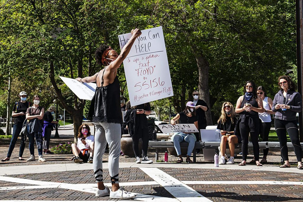 Jenelle Figgins holds up signs with instructions on how to help get justice for George Floyd while standing next to Wagner Park on Sunday, May 31, 2020. (Kelsey Brunner/The Aspen Times)