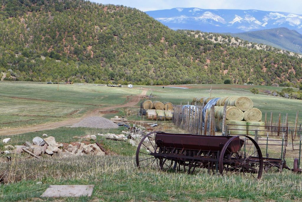 A stony irrigation channel runs past rolled hay on the Crystal River Ranch, just below Dry Park Road, with Basalt Mountain in the background. The pond in the lower field, to the right of the white trailer, drains to the Roaring Fork River and is the approximate location for a potential 55-foot-tall dam that would hold 500 acre-feet of water.