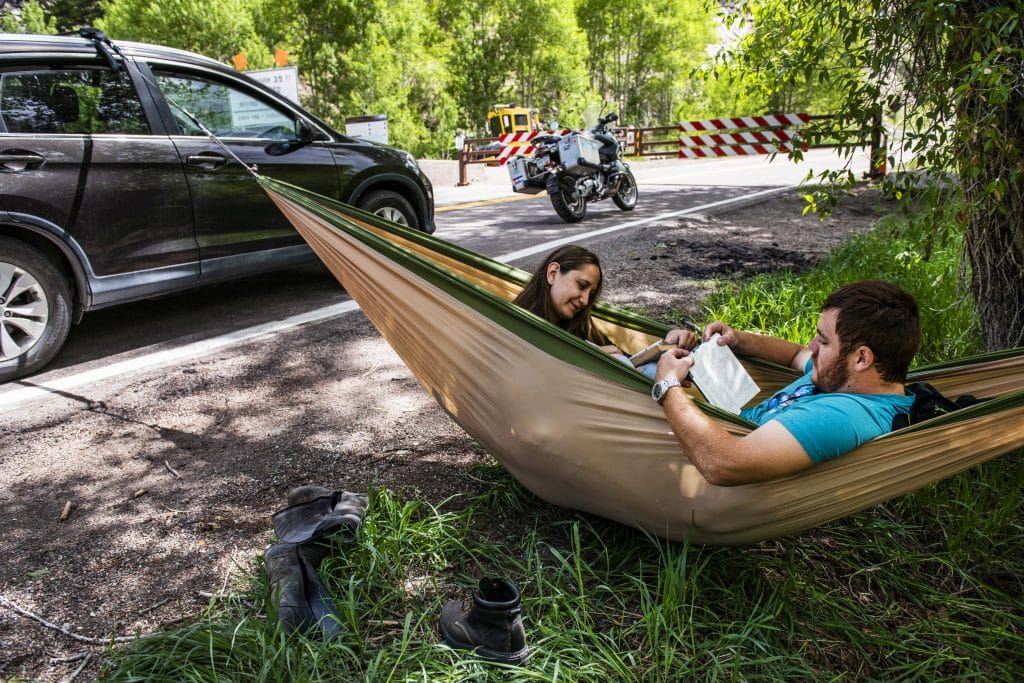 "Mariah Lee, left, and Adolfo Verduzco swing in a hammock as they wait to be the first people to drive up Independence Pass from the Aspen side on opening day on Monday, June 1, 2020. Verduzco has lived in the Roaring Fork Valley for 22 years and said he has always wanted to be the first person to go up the pass when the gate opens for the season. ""This is the first year we can make it work,"" said Lee. The two arrived at the gate at 10 p.m. the night before and slept in their car to be the first in line."